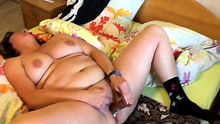 Fat mature wife lies on the bed and fucks herself to orgasm