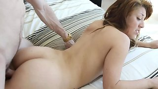 A redhead is getting kisses and she is also penetrated on the bed